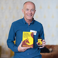 David Parrish international creative industries speaker and author holding paperback book and eBook on iPhone
